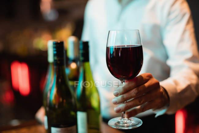 Середине раздел бармен Холдинг стакан красного вина на барной стойкой — стоковое фото