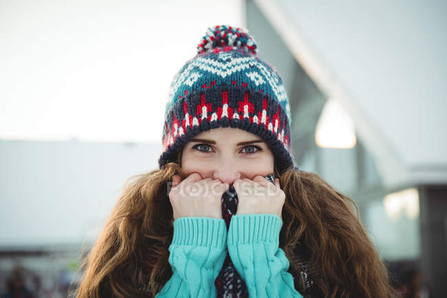 Portrait of beautiful woman in warm clothing covering her mouth with jumper — Stock Photo
