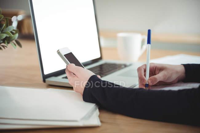 Business executive scrittura sul diario durante l'utilizzo del telefono cellulare in ufficio — Foto stock