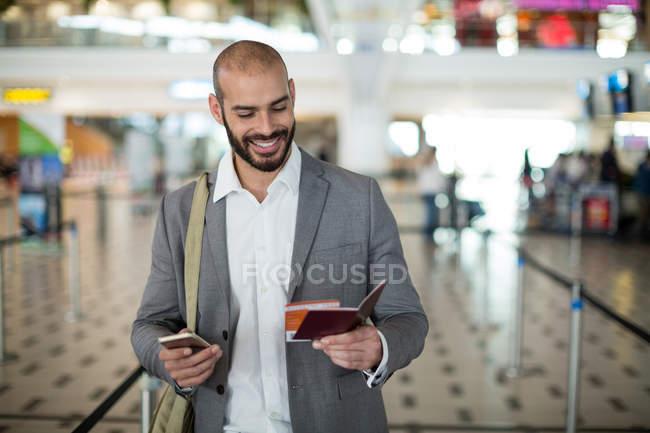Sonriente hombre de negocios sosteniendo una tarjeta de embarque y comprobar su teléfono móvil en la terminal del aeropuerto - foto de stock