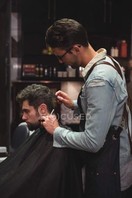 Uomo ottenere capelli tagliati da parrucchiere con rasoio in negozio di barbiere — Foto stock