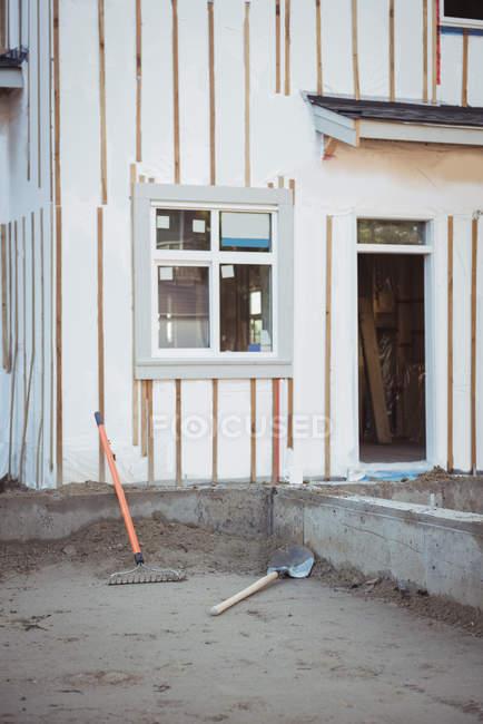 Граблі і лопатою перед будинком на будмайданчик — стокове фото