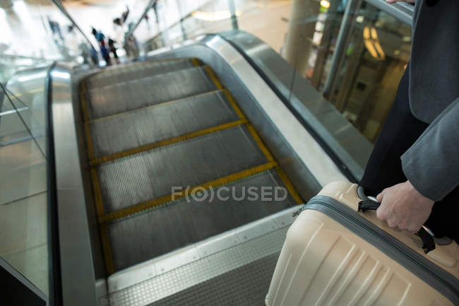Businesswoman with luggage moving down on escalator at airport terminal — Stock Photo