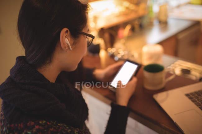 Donna che utilizza il telefono cellulare al bancone della cucina in casa — Foto stock