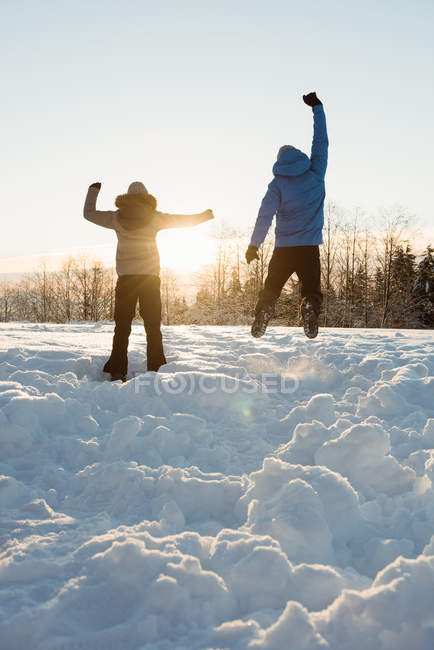 Rear view of couple jumping on snowy landscape — Stock Photo
