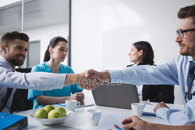 Лікарі рукостискань один з одним у зустрічі в конференц-залі — стокове фото