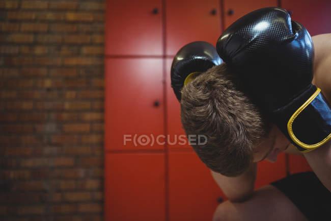 Boxer stressato seduto con guanti da boxe nello spogliatoio — Foto stock