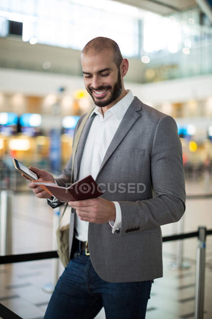 Smiling businessman holding a boarding pass and checking his mobile phone at airport terminal — Stock Photo