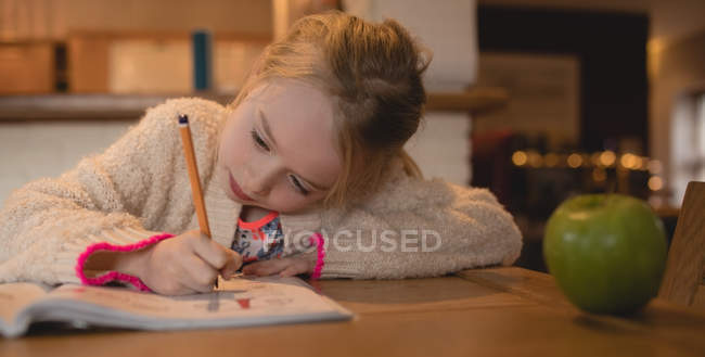 Attentive girl doing homework in living room at home — Stock Photo