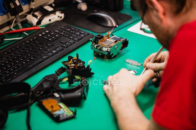 Man repairing mobile phone in repair centre — Stock Photo