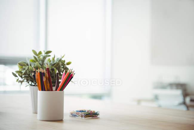 Stifthalter und Topfpflanze auf dem Tisch im Büro — Stockfoto