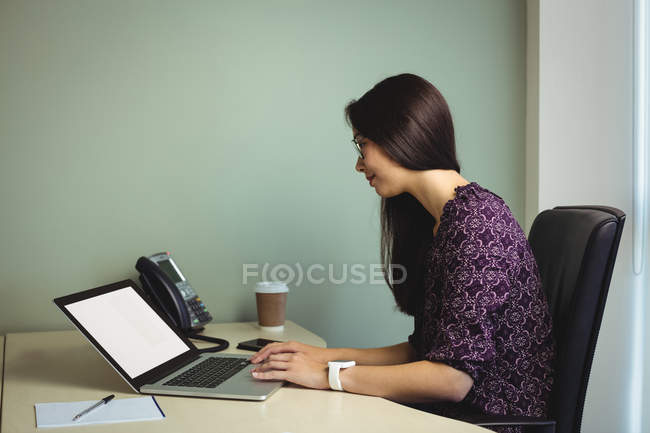 Businesswoman working on laptop in office — Stock Photo