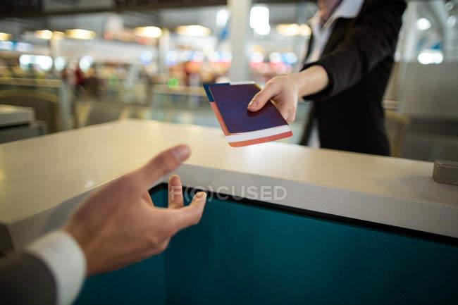 Línea aérea llegadas asistente dando pasaporte a viajero en mostrador en la terminal del aeropuerto - foto de stock
