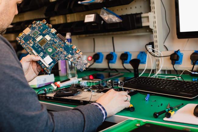 Mann repariert Laptop in Werkstatt — Stockfoto