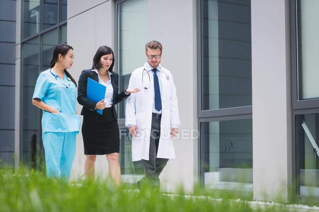 Doctors and nurse interacting while walking in hospital premises — Stock Photo