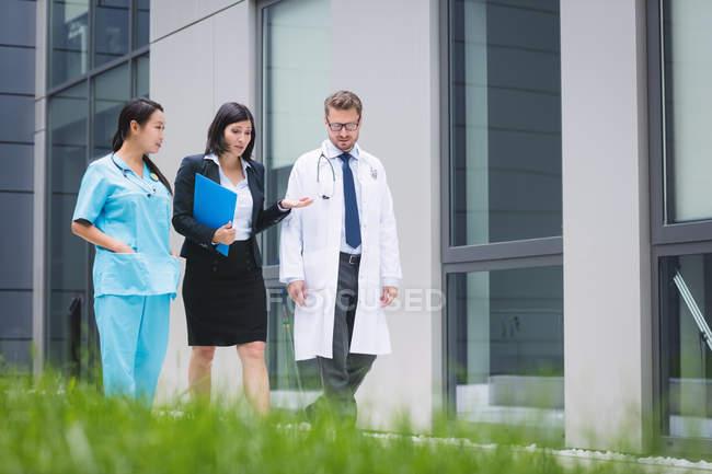 Médicos e enfermeira interagindo enquanto caminhava nas instalações do hospital — Fotografia de Stock
