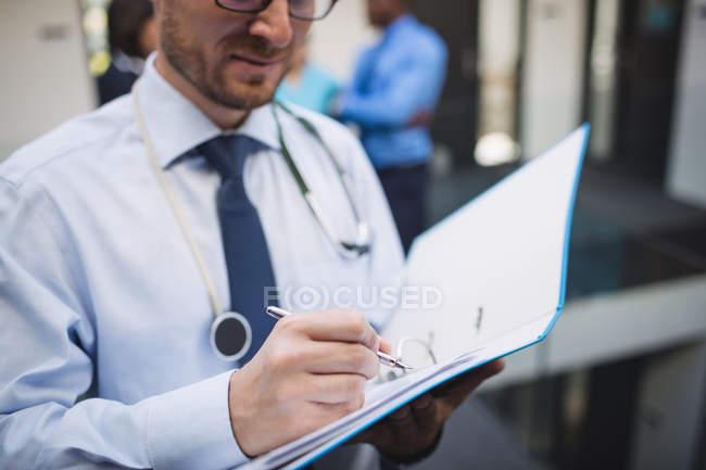 Médico a escrever um relatório médico no corredor do hospital — Fotografia de Stock