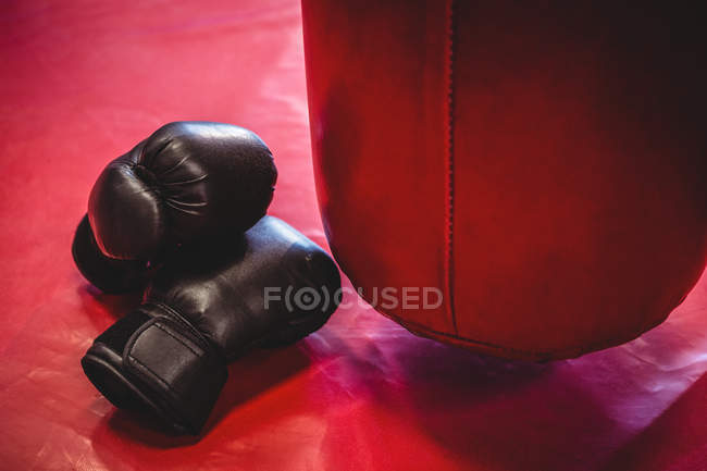 Boxing gloves and punching bag on red surface in fitness studio — Stock Photo
