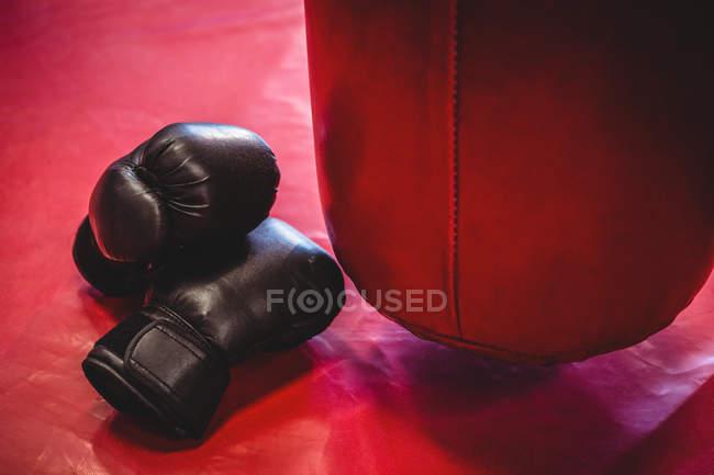 Guanti da boxe e sacco da boxe sulla superficie rossa in palestra — Foto stock