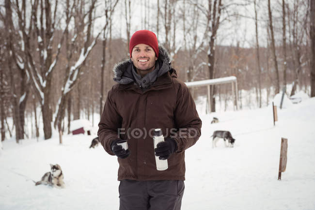 Musher hält Thermoskanne im Winter — Stockfoto