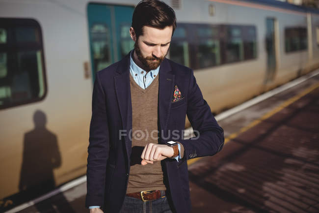 Businessman checking time on smartwatch at railway station — Stock Photo