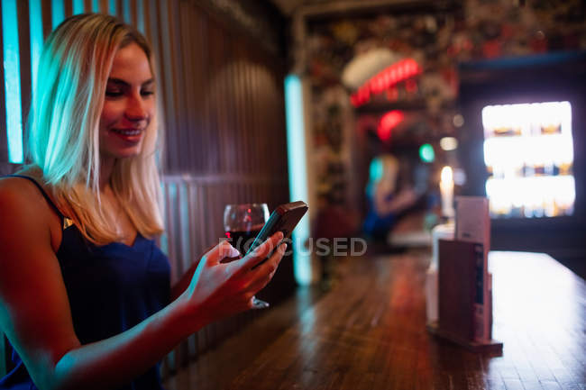 Beautiful woman using mobile phone while having red wine at counter in bar — Stock Photo