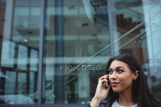 Woman talking on mobile phone outside the office building — Stock Photo