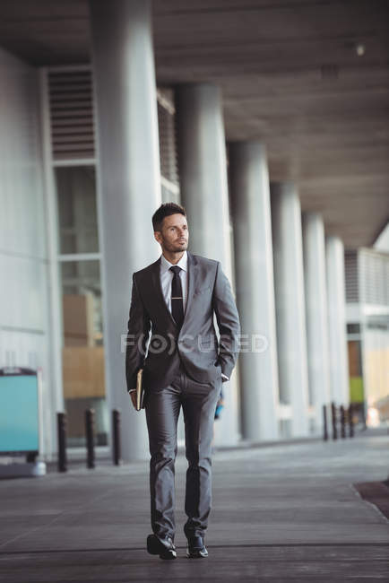 Businessman with a diary walking in office building corridor — Stock Photo