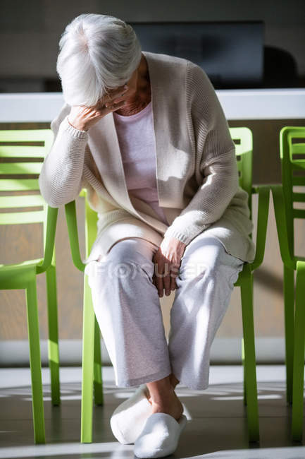Tensed senior woman sitting on chair in waiting area of hospital — Stock Photo