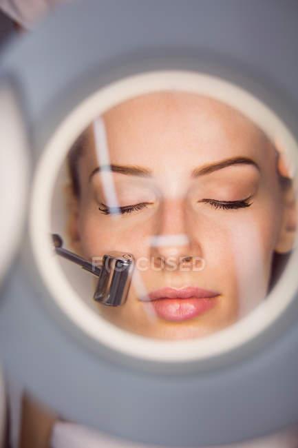 Крупный план дерматолога, выполняющего лазерную эпиляцию лица пациента в клинике — стоковое фото