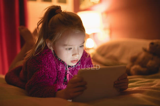 Girl lying on front on bed and using digital tablet in bedroom at home — Stock Photo