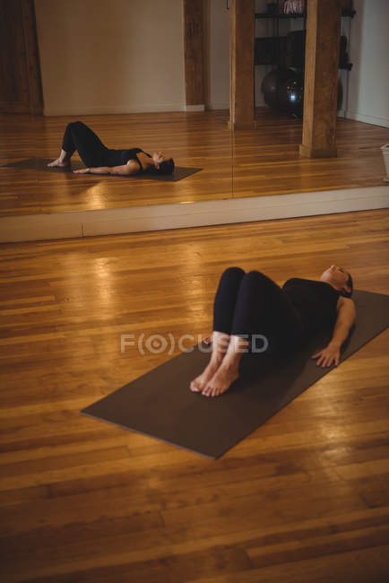 Женщина практикует йогу на коврике в фитнес-студии — стоковое фото