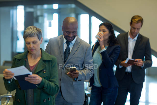Business commuters waiting in queue at airport — Stock Photo