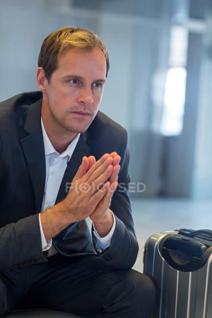 Напряженный бизнесмен сидит в зале ожидания с багажом в терминале аэропорта — стоковое фото