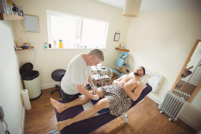Fisioterapista che esegue l'ago secco sul ginocchio del paziente di sesso maschile in clinica — Foto stock