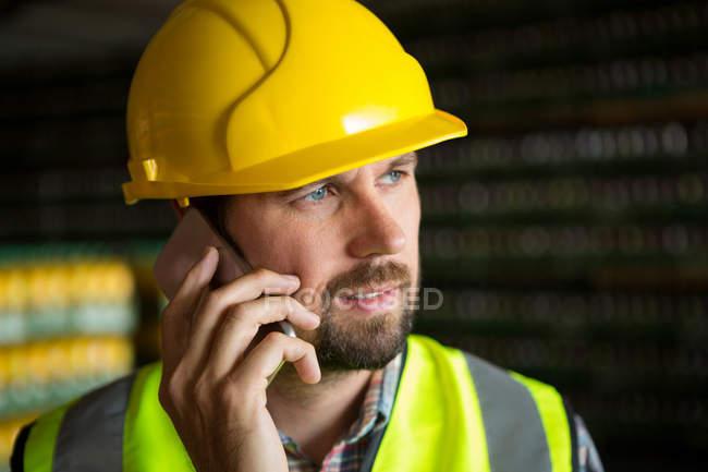 Nahaufnahme eines männlichen Arbeiters, der in der Fabrik telefoniert — Stockfoto