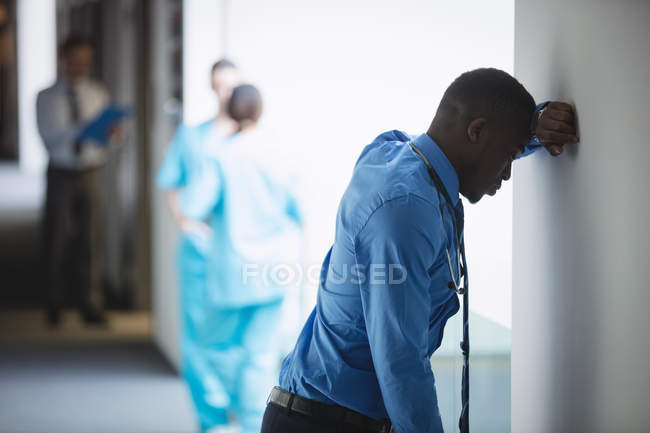 Sad doctor leaning on wall in hospital corridor — Stock Photo