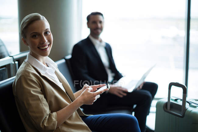 Portrait of smiling commuters sitting in waiting area at airport terminal — Stock Photo