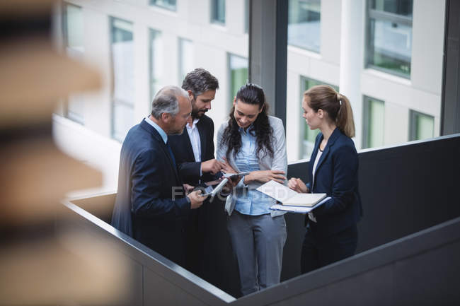 Group of business people having a discussion near staircase in office — Stock Photo