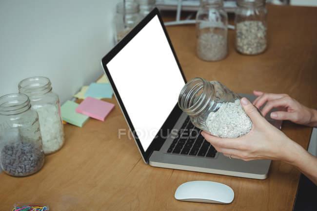 Esecutivo aziendale che utilizza il computer portatile mentre tiene il vaso di ciottoli in ufficio — Foto stock
