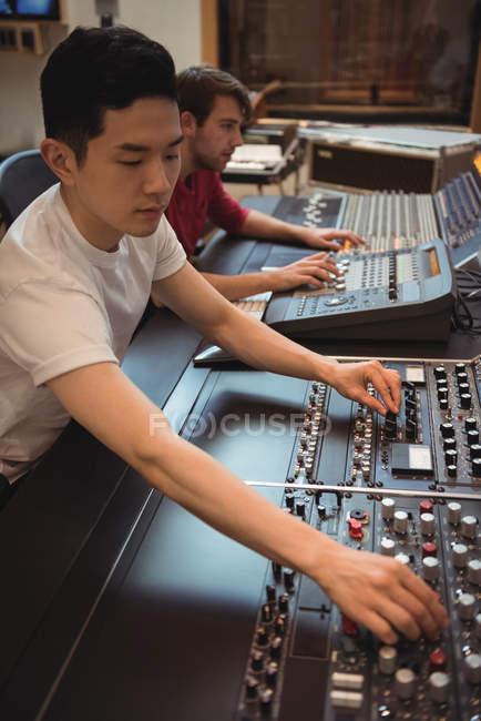 Audio engineers using sound mixer in recording studio — Stock Photo