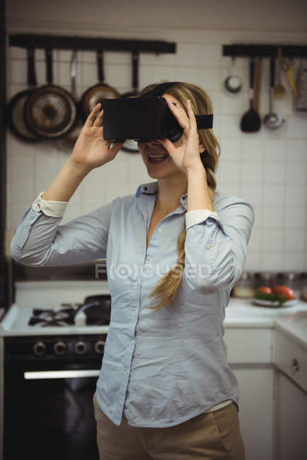 Woman experiencing virtual reality headset in kitchen at home - foto de stock