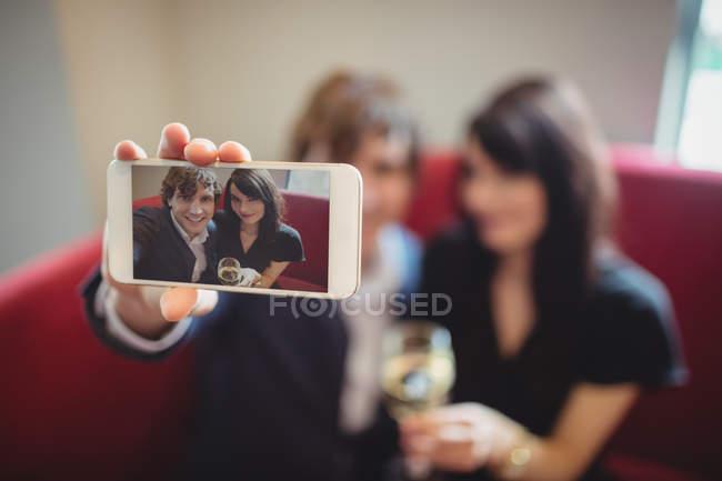 Paar trinkt und macht ein Selfie im Restaurant — Stockfoto