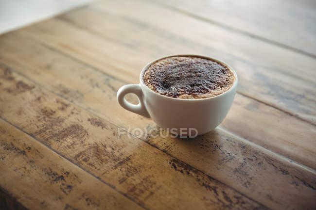 Taza de café en una mesa en la cafetería - foto de stock