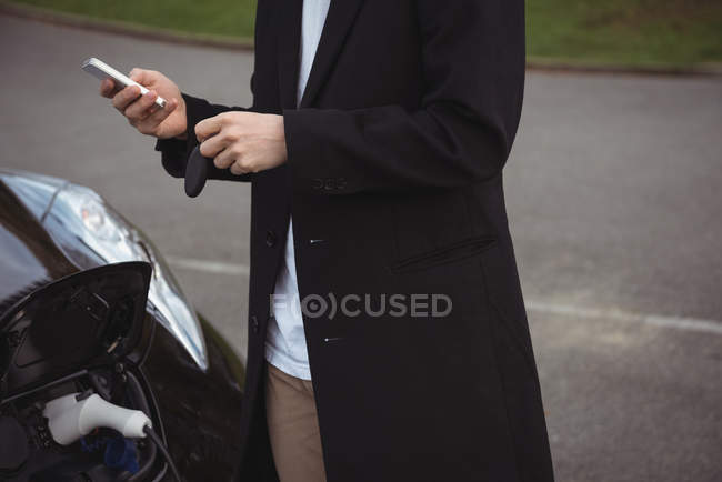 Mann benutzt Handy beim Laden von Elektroauto auf der Straße — Stockfoto