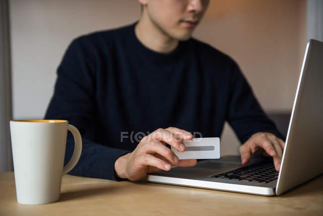 Homme faisant des achats en ligne sur ordinateur portable à la maison — Photo de stock