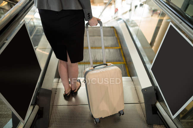 Low section of businesswoman standing on escalator with luggage at airport — Stock Photo