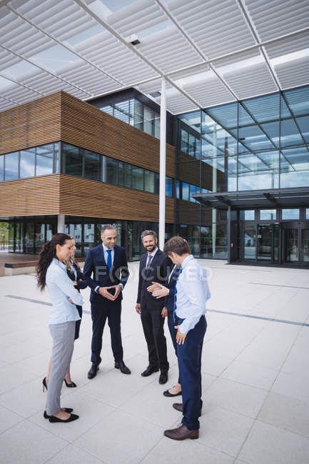Group of cheerful businesspeople interacting outside office building — Stock Photo