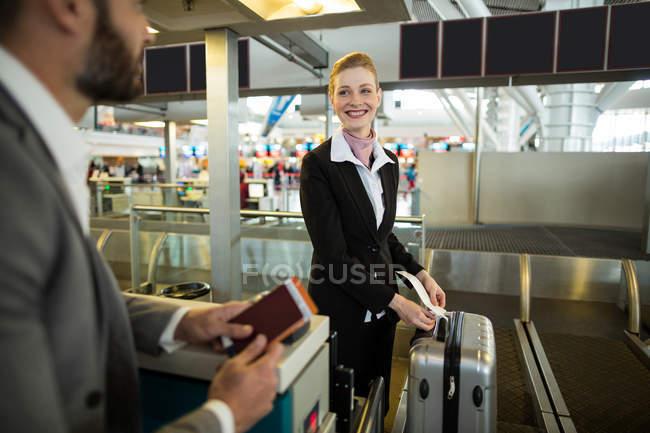 Авіакомпанія-Реєстрація attendant прилипання тег до багажу приміських в аеропорту — стокове фото