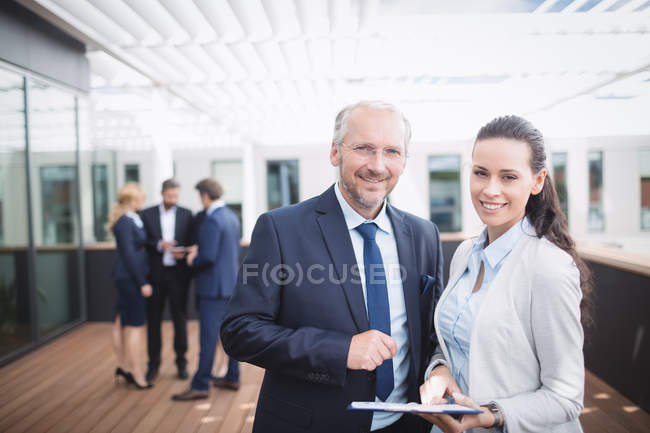 Portrait of businessman discussing over document with colleague in office — Stock Photo